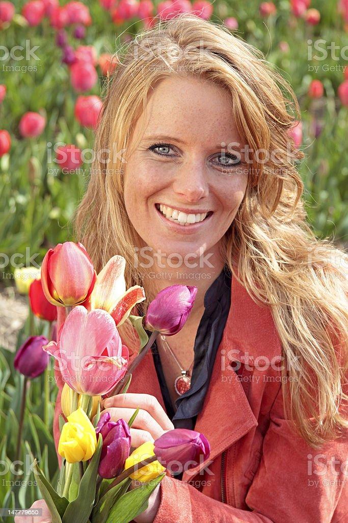 Dutch woman between de flower fields in the Netherlands royalty-free stock photo