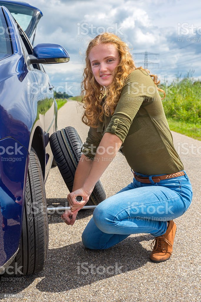 Dutch woman changing car tire on country road stock photo