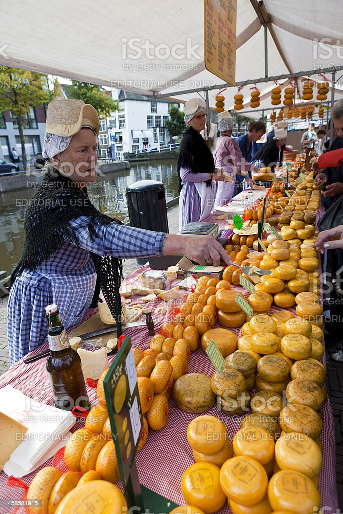 Dutch Woman Selling Cheese in Outdoor Market Alkmaar Netherlands stock photo