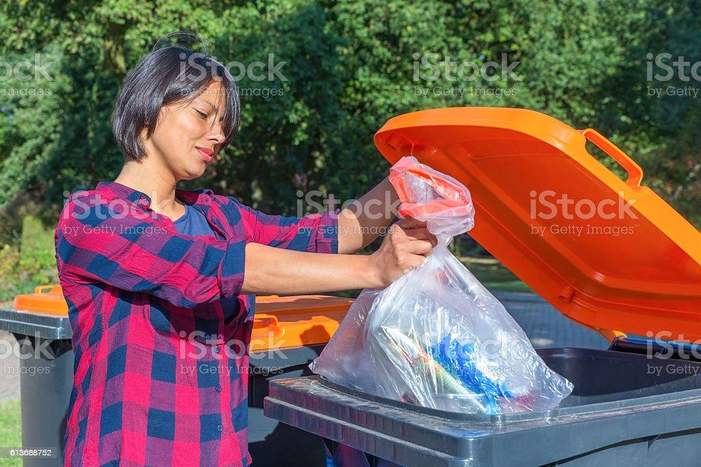 Dutch woman throwing plastic garbage in thrash bin stock photo