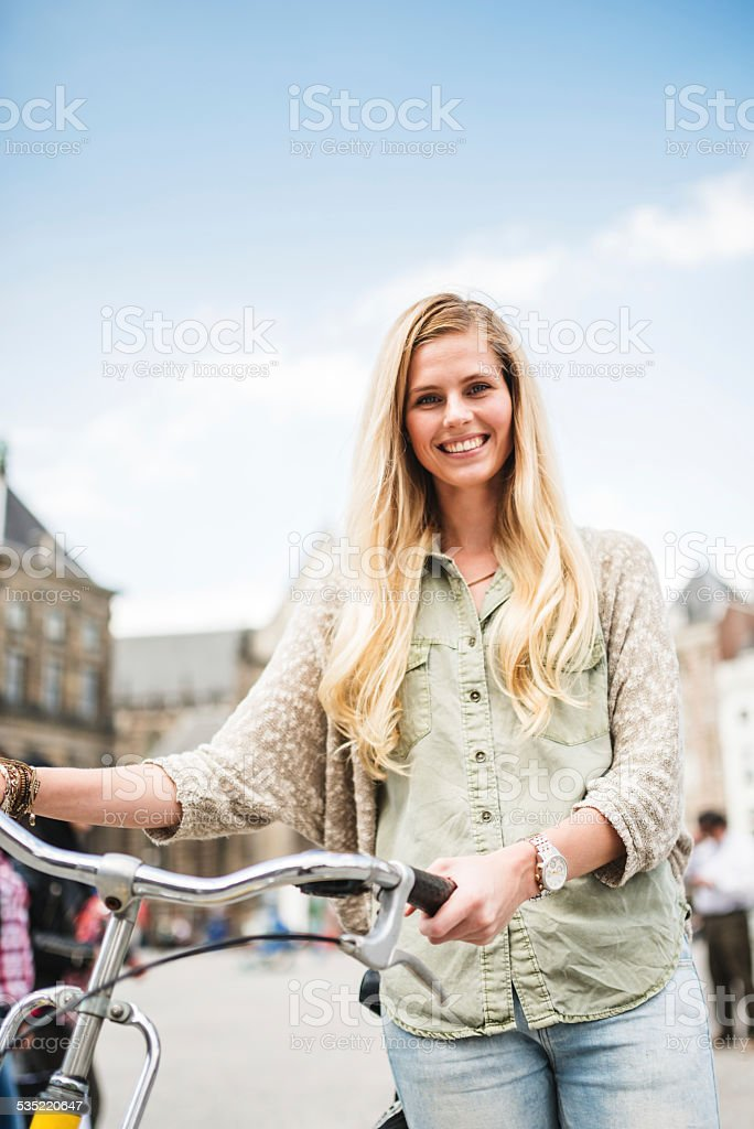 Dutch woman with bicycle in amsterdam dam square stock photo