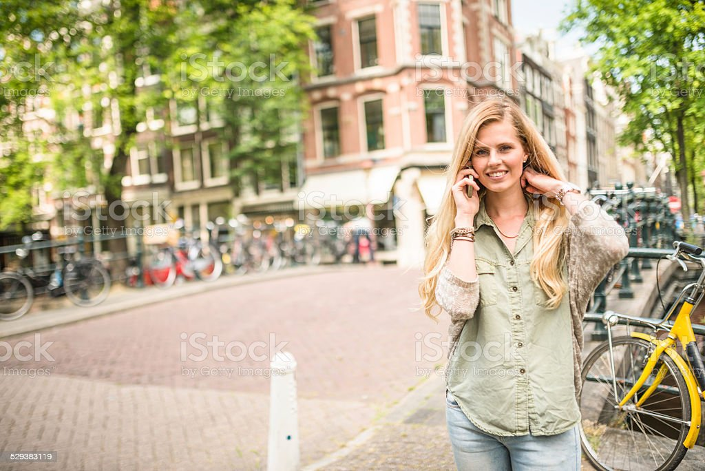 Dutch woman with bicycle in amsterdam on the phone stock photo