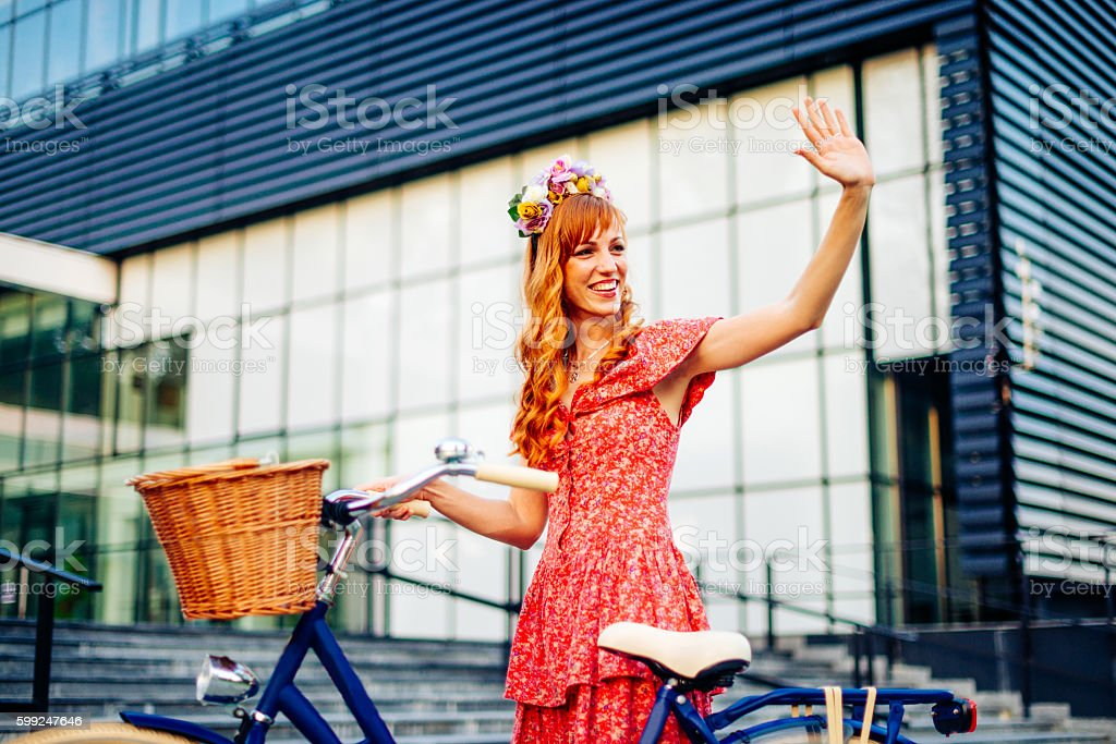 Dutch woman with ginger hair and bicycle waving to friends stock photo