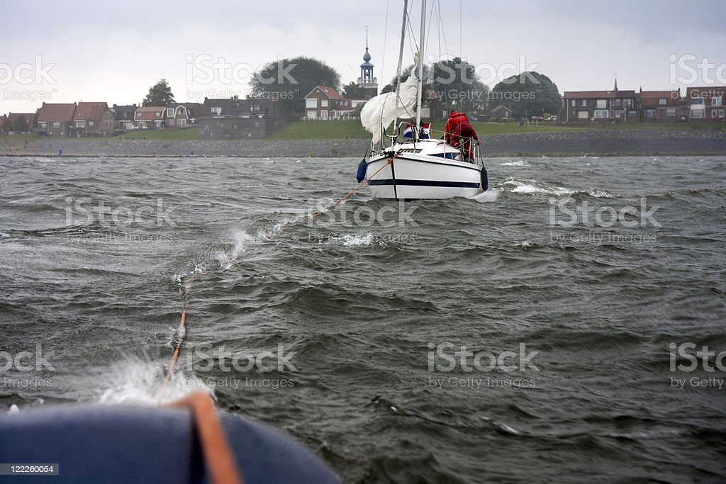 Dutch yacht in misery needs help from a tugboat stock photo