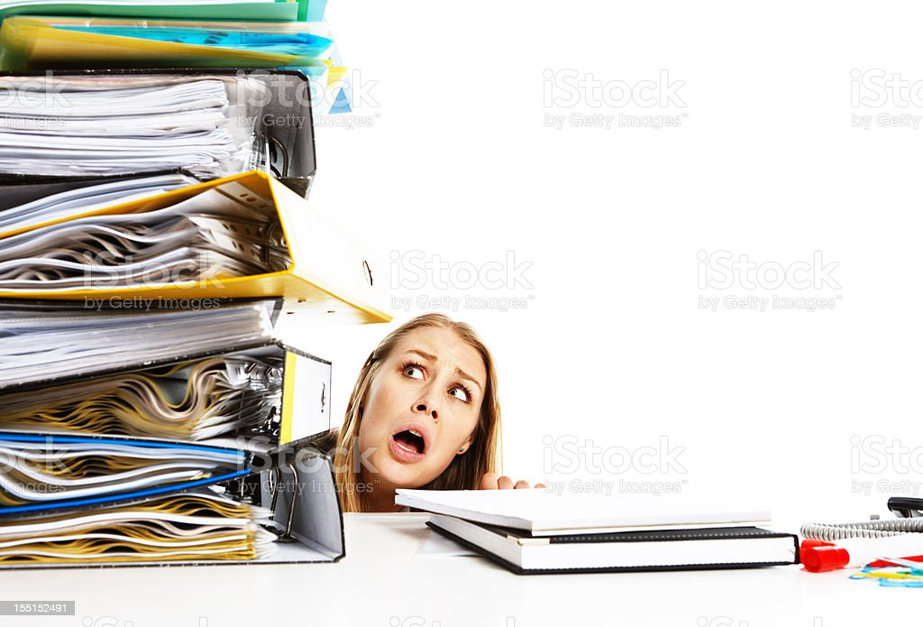 Dwarfed by workload young businesswoman looks up in horror royalty-free stock photo