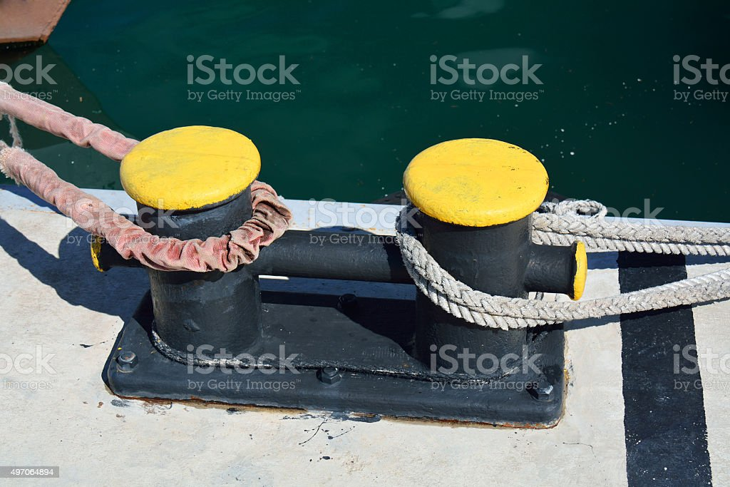 Dyed metal bitt with a velvet rope stock photo