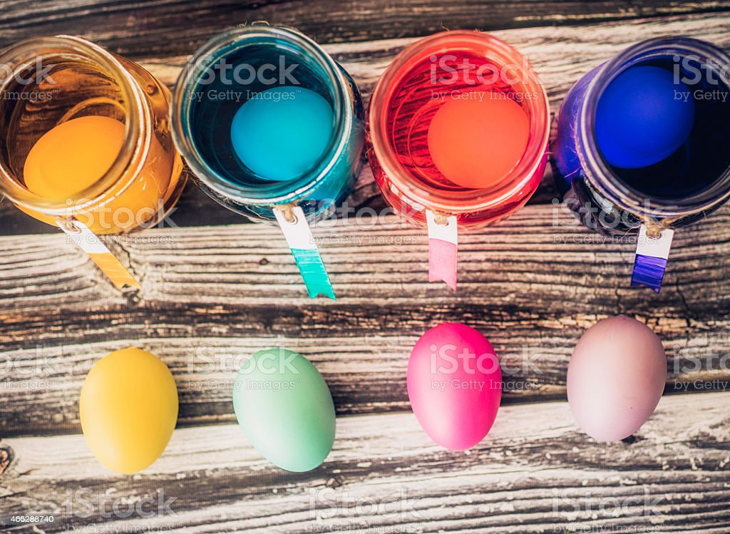 Dyeing eggs for Easter. Eggs in dye and eggs drying. stock photo