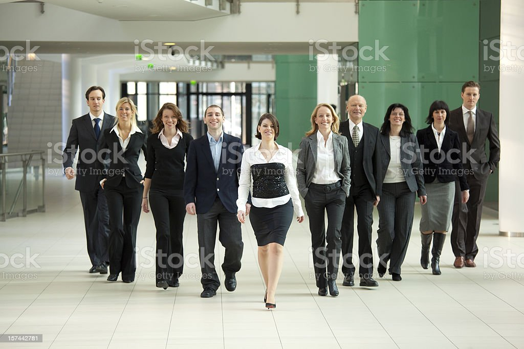 dynamic businessteam walking to camera in corridor royalty-free stock photo