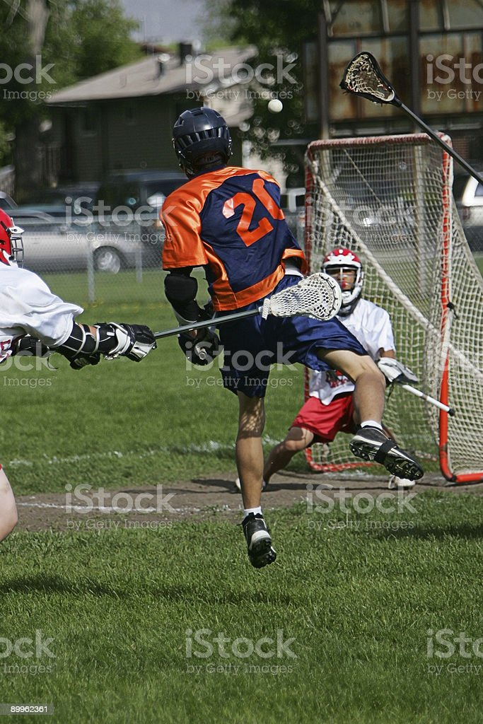Dynamic Male Lacrosse Player Fires Ball at Goal royalty-free stock photo