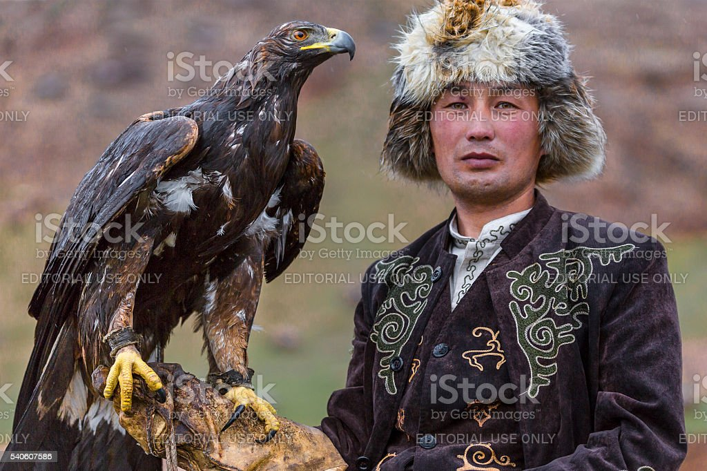 Eagle hunter holding his golden eagle. stock photo