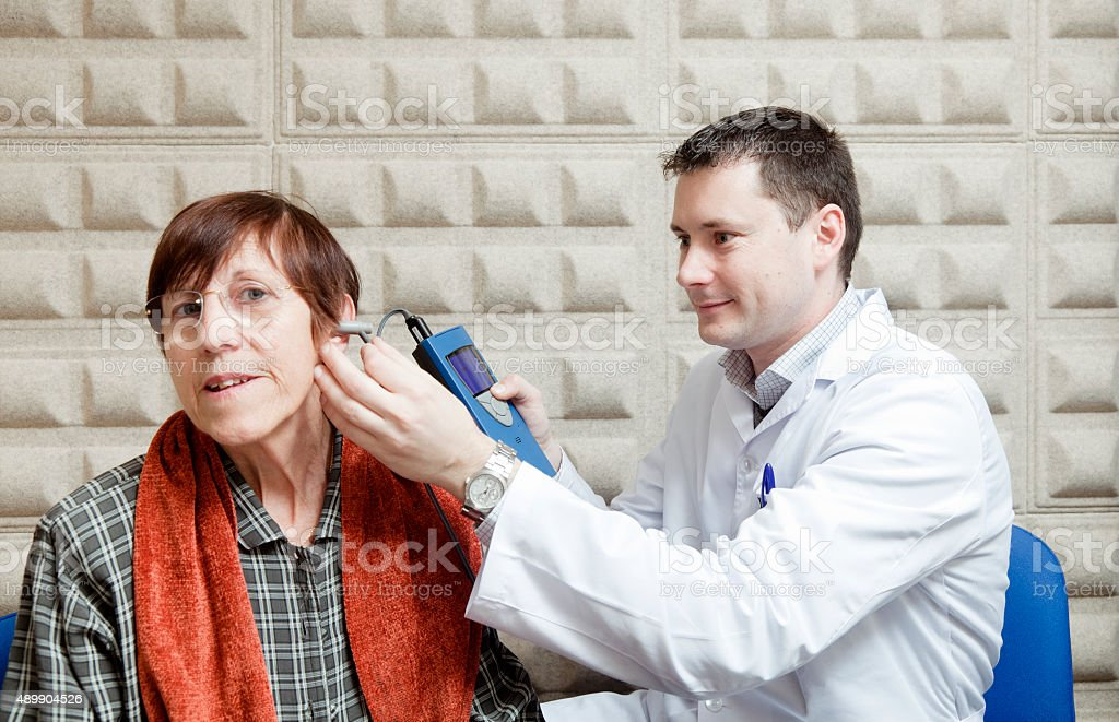 Ear exam on an old lady stock photo