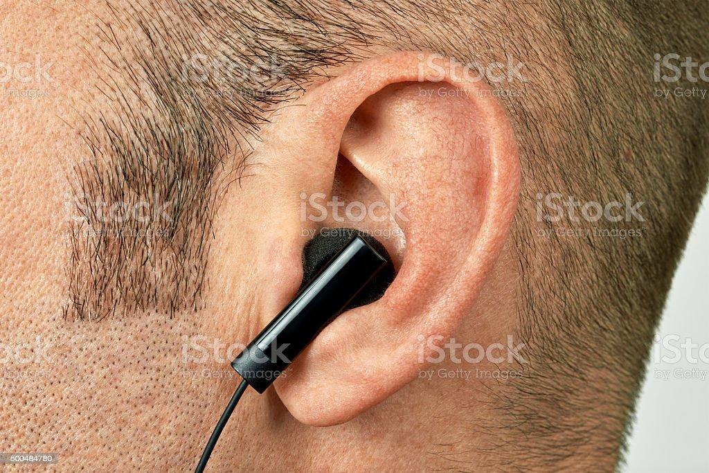Ear with earphone closeup stock photo