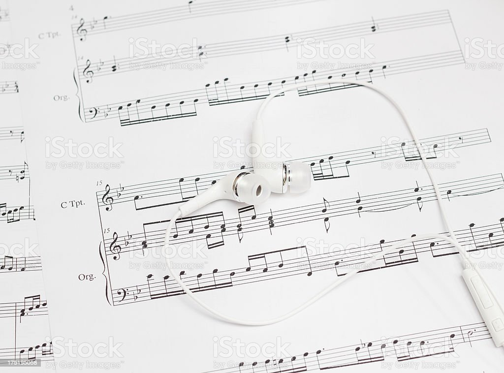 earbuds and sheet music stock photo