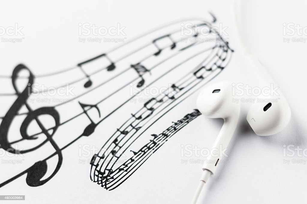 Earbuds on music notes stock photo