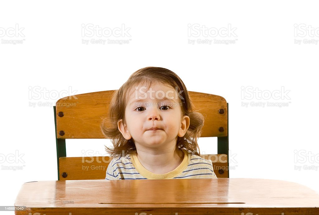 Early education baby boy sitting at school desk royalty-free stock photo