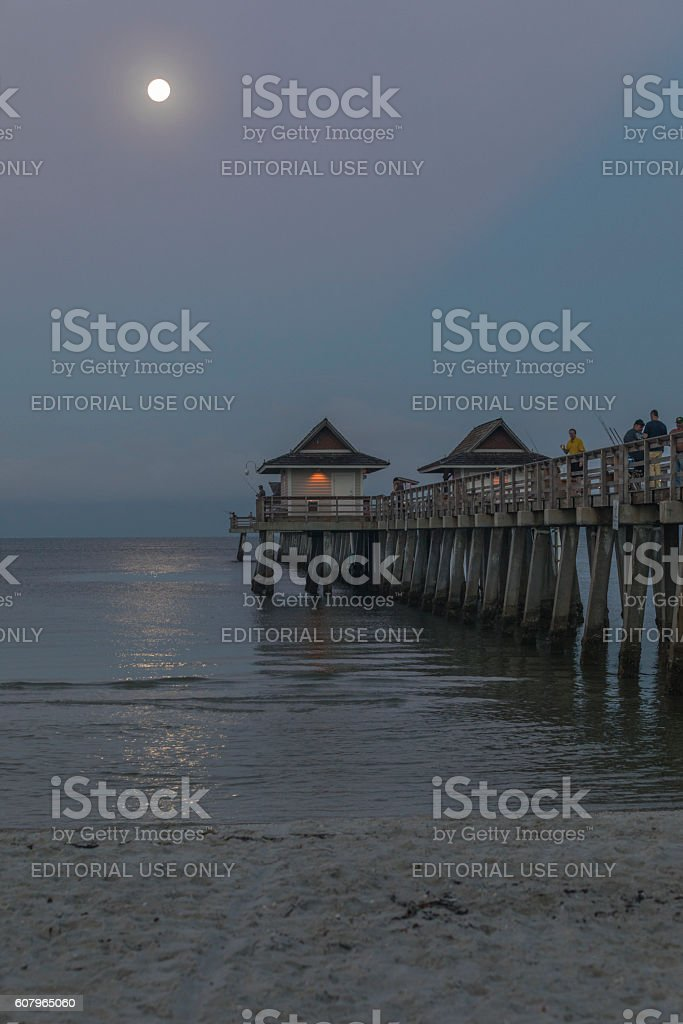 Early Morning Fishermen Fish Off the Naples Pier stock photo