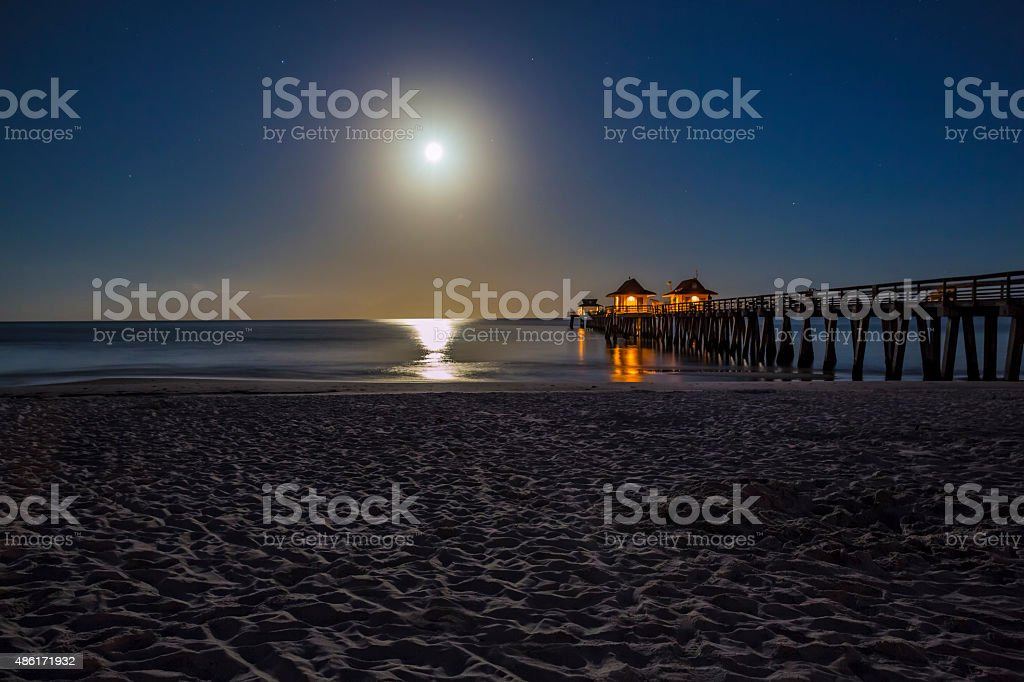 Early Morning Full Moon Over the Naples Pier and Beach stock photo