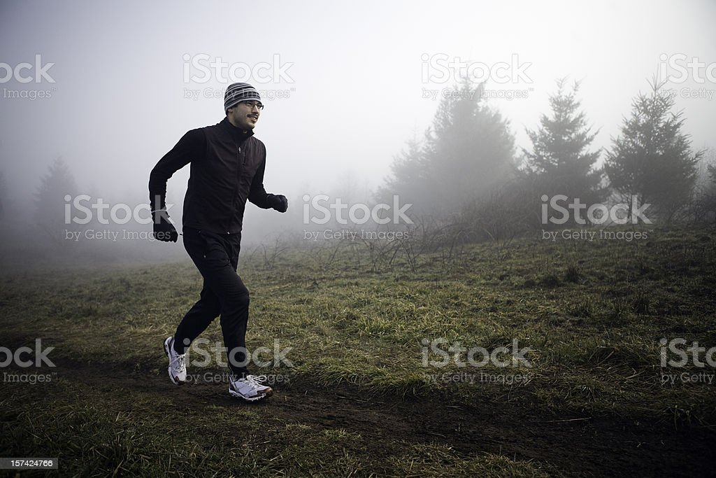 Early Morning Jogger Running in the Fog royalty-free stock photo