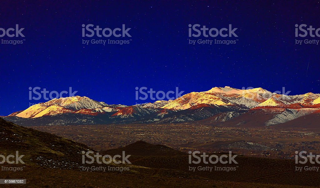 Early morning Snowy mountain landscape with starry sky. stock photo