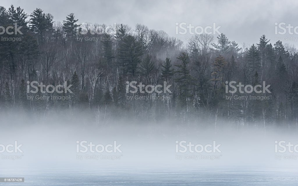 Early spring fog, warm air, and thawing Eastern Ontario lake. stock photo