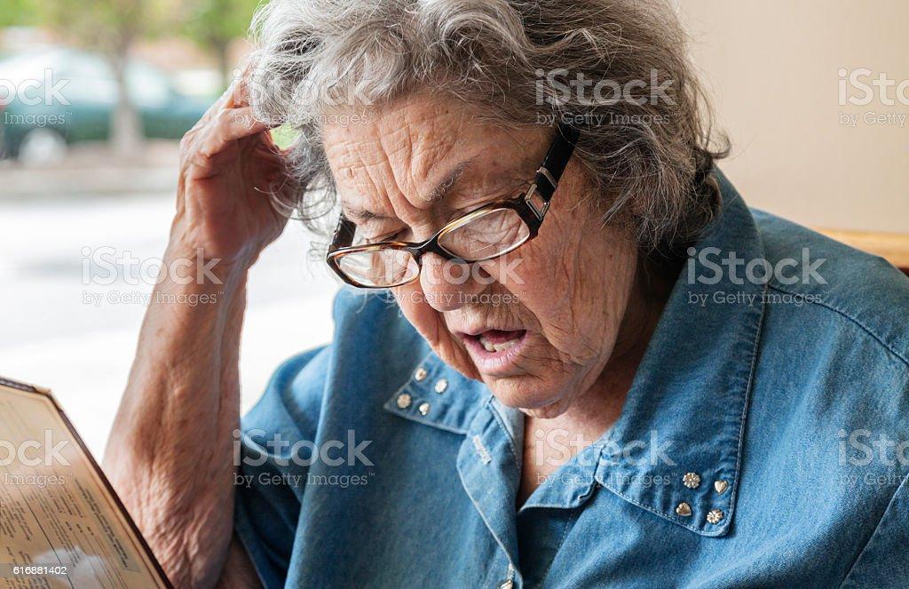 Early Stage Dementia Elderly Woman Reading Restaurant Menu stock photo
