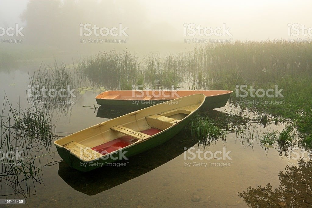 Early sunlight on two wooden boats moored in foggy lake stock photo