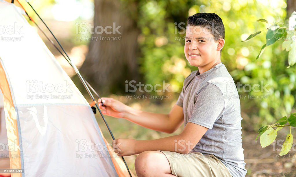 Earlyteen boy putting a tent up for a weekend camping adventure stock photo