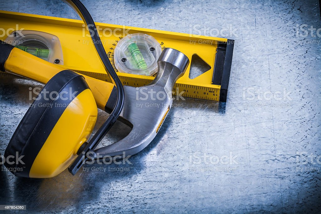 Earmuffs construction level claw hammer on scratched metallic ba stock photo