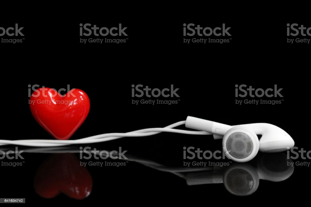Earphone and a red heart on the black background stock photo