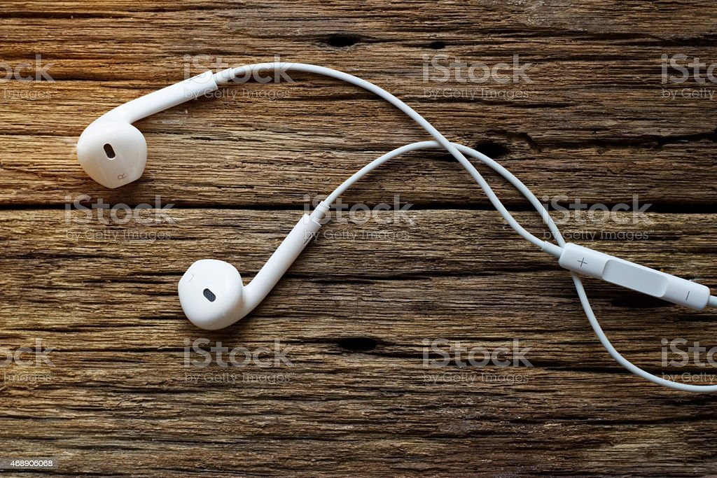 earphones and vibrant lighting on rotten wooden background stock photo