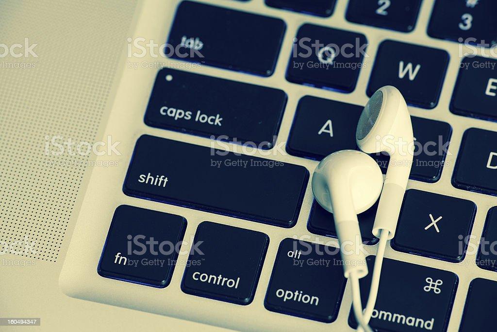 Earphones on Computer Keyboard royalty-free stock photo