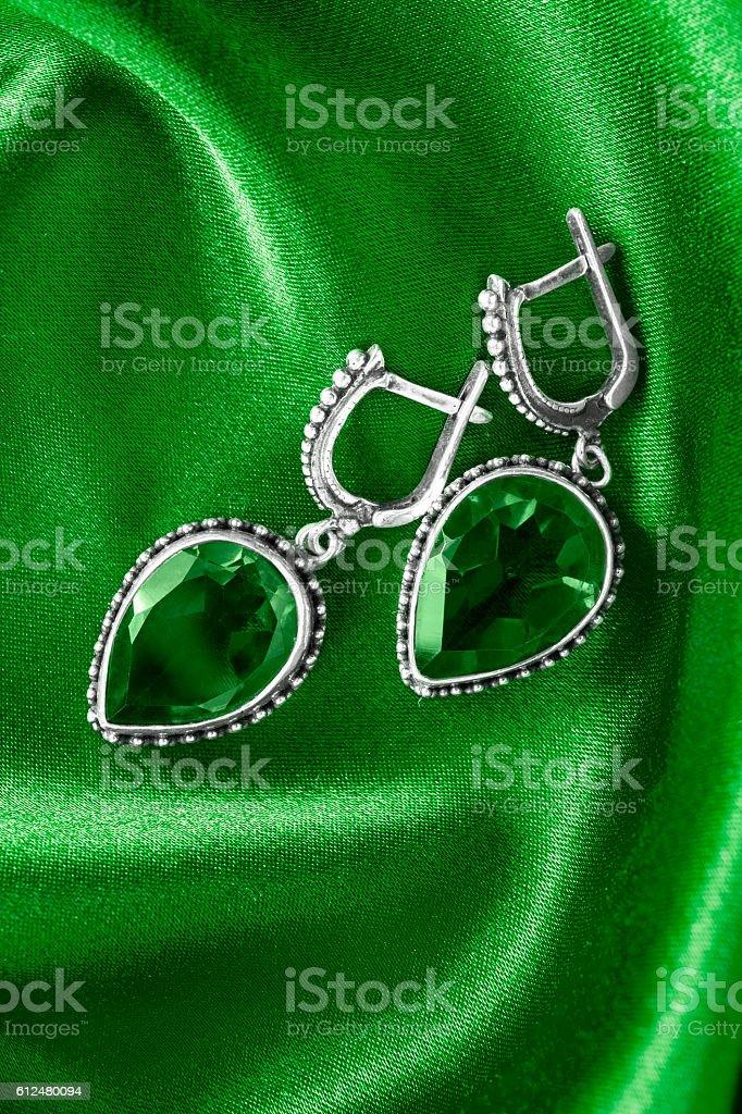 Earrings on silk stock photo