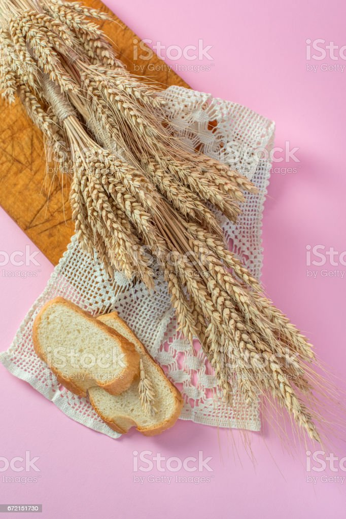 Ears of wheat and white bread rusks on a wooden board from above stock photo