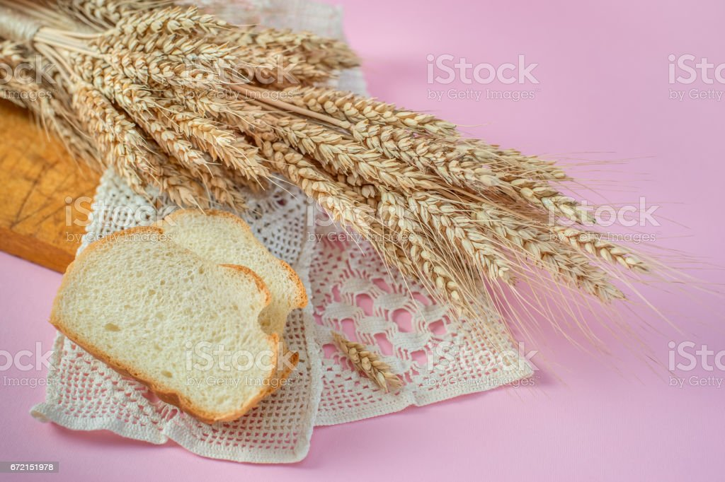 Ears of wheat and white bread rusks on a wooden board stock photo