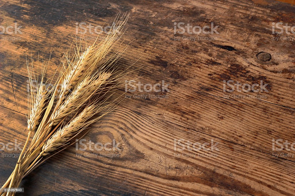 Ears of wheat on wooden table stock photo