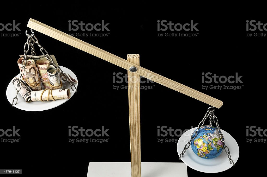 Earth and Money on a Two Pan Balance royalty-free stock photo
