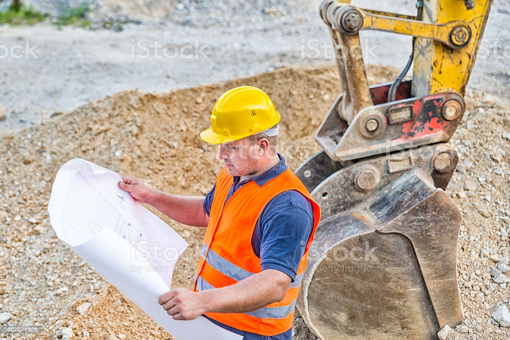 Earth Digger Driver checking blueprint stock photo