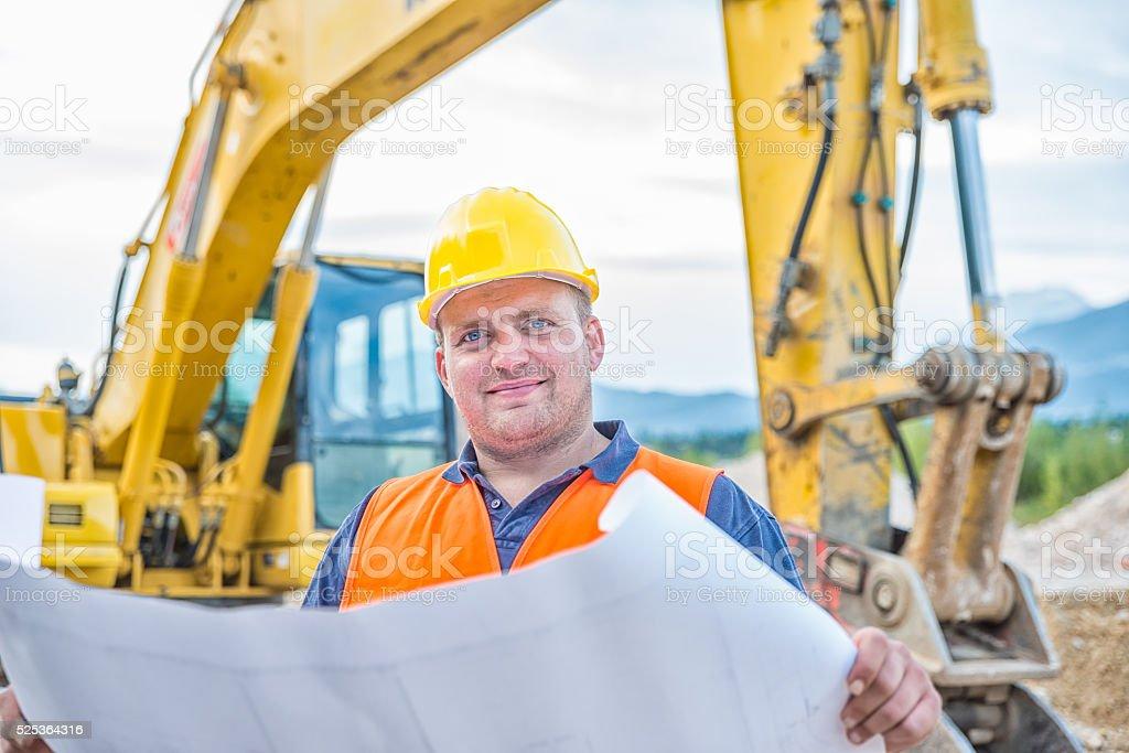 Earth Digger Driver checking blueprint stock photo
