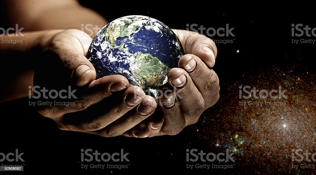 Earth in the palm of two hands with a galaxy background stock photo