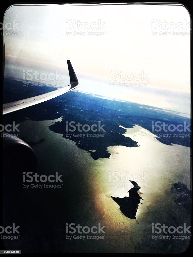Earth landscape view from airplane porthole on sunset stock photo