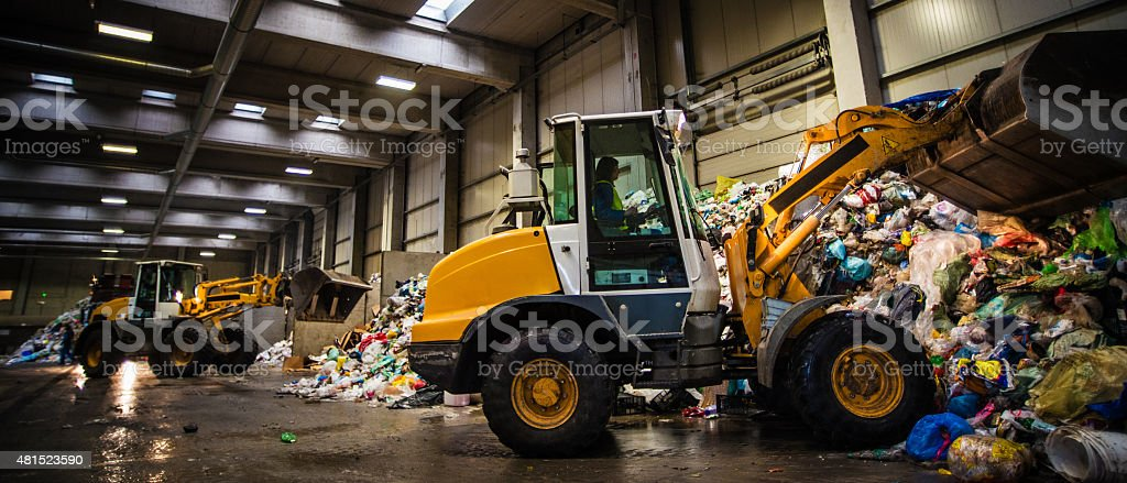 Earth mover in the junkyard with female worker stock photo
