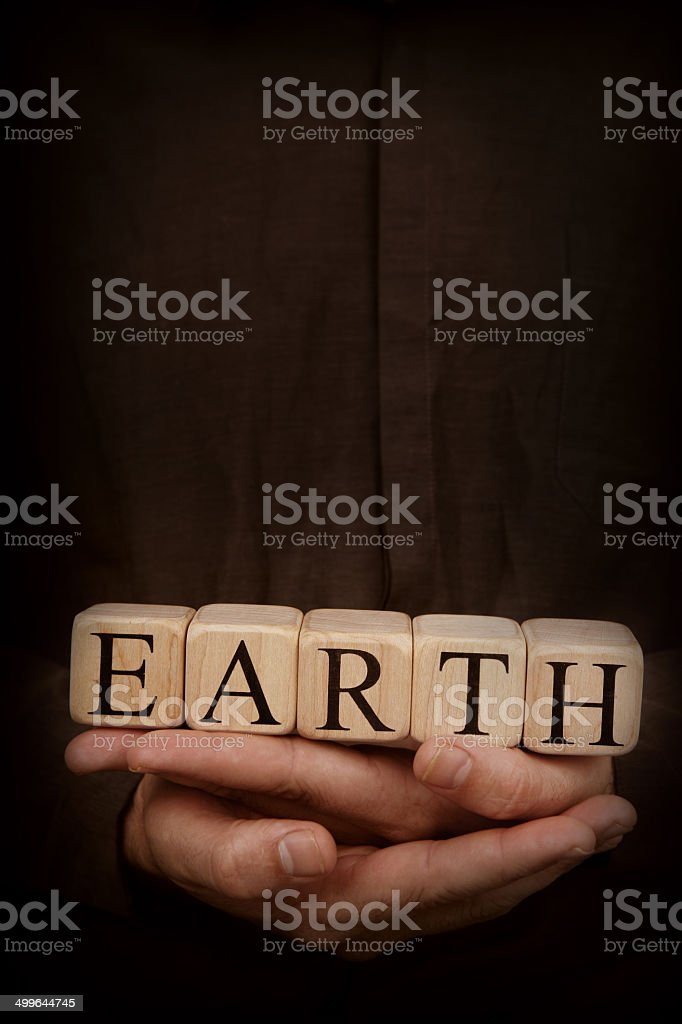 Earth - Toy Blocks in Hands on Dark Background royalty-free stock photo