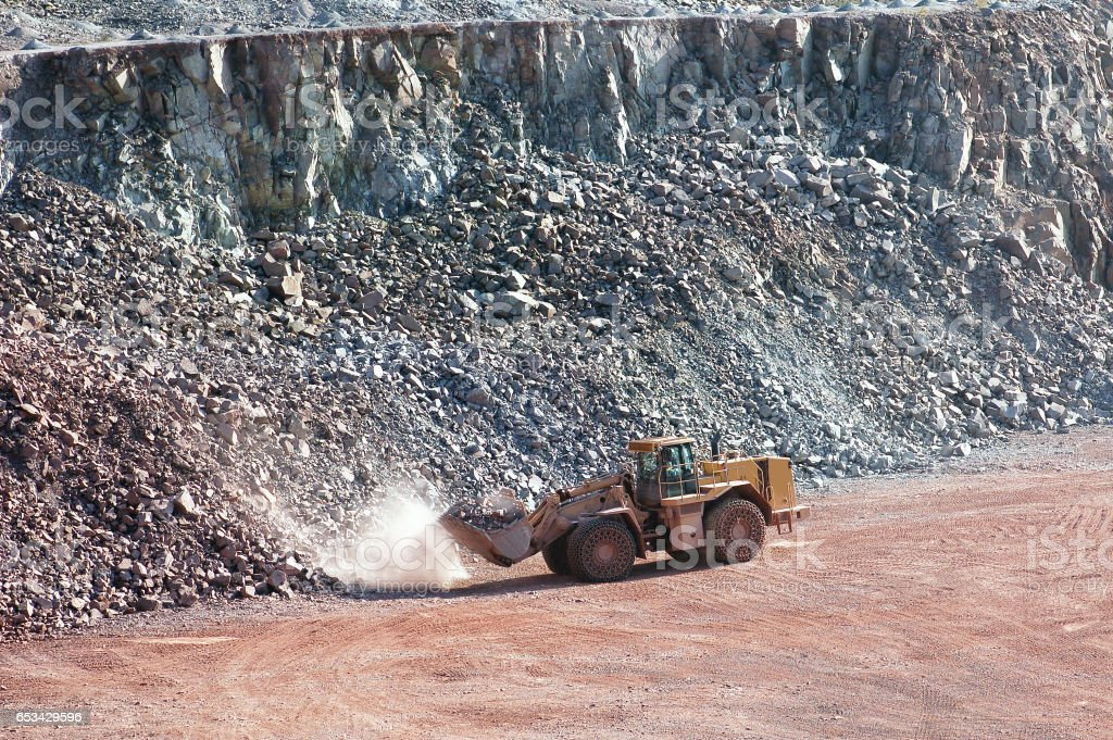 Earthmover working in quarry mine. stock photo