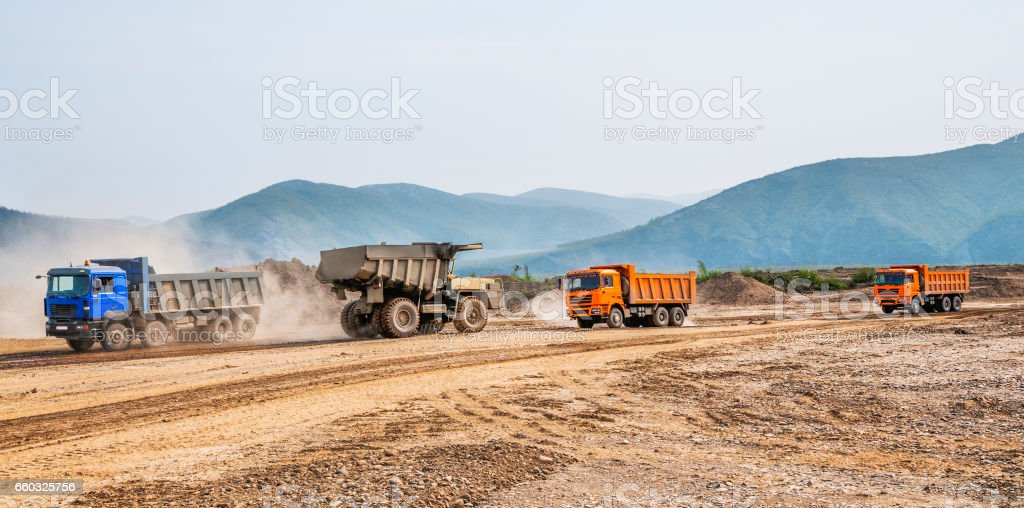 Earthworks. Cargo dump trucks carry ground to the construction site. stock photo