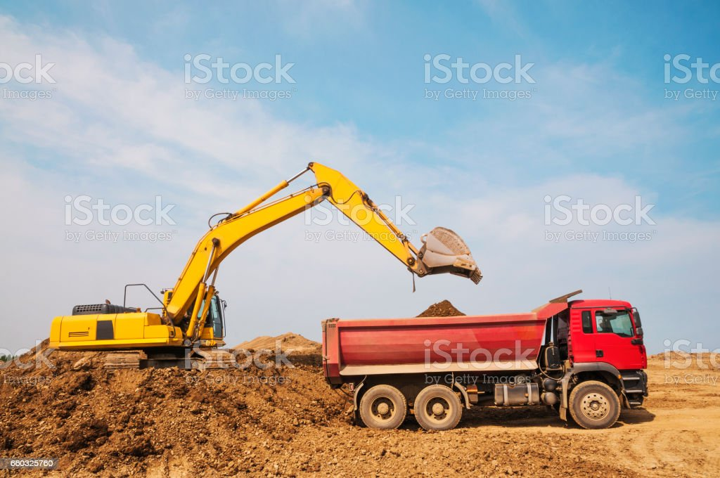 Earthworks. Loading of the earth into the body of a cargo dump truck. stock photo