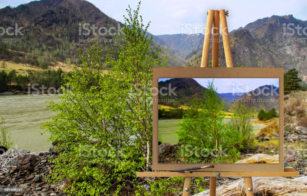 Easel  Altai Mountains on a canvas on a landscape. stock photo