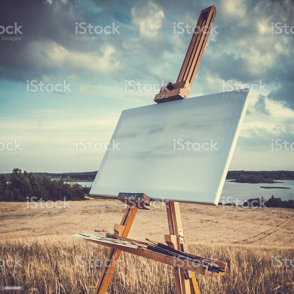 easel on lake landscape, retro stylized stock photo