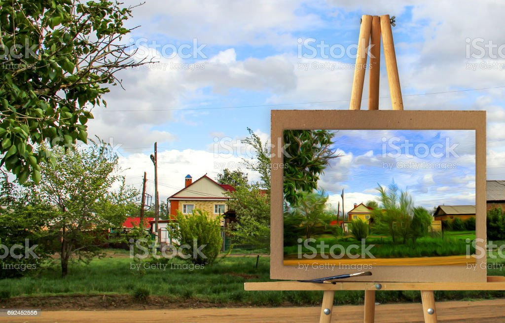 Easel with a painting watercolor rural landscape with village garden stock photo