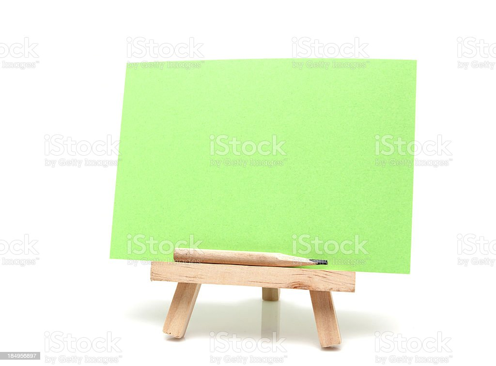 Easel with blank green paper and pencil isolated royalty-free stock photo