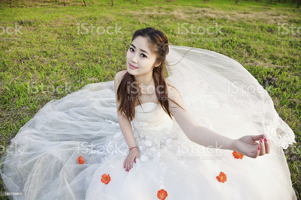 East Asian bride lying on the grass royalty-free stock photo